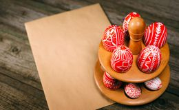 Easter eggs with folk white pattern lay around stand for eggs standing on wood board. Closeup Top view royalty free stock photography