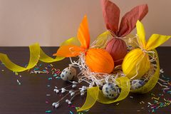 Easter eggs in form of rabbit in the nest with willow branch, yellow ribbon and quail eggs. stock photos