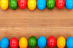 Easter eggs framing an old wooden table surface Stock Images