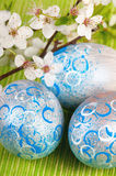 Easter eggs with fresh blossom. Easter eggs painted in silver with abstract, modern blue and white patterns, decorated with fresh plum blossom on green fabric royalty free stock photos