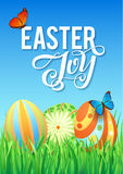 Easter eggs in Fresh Green Grass. Decorated Easter Eggs in Grass on Sky Background. Happy Easter Calligraphy Poster Royalty Free Stock Image