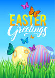 Easter eggs in Fresh Green Grass. Decorated Easter Eggs in Grass on Sky Background. Happy Easter Calligraphy Poster Stock Photos