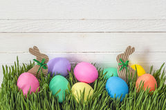 Easter eggs in fresh green grass on white  wooden background. Royalty Free Stock Image