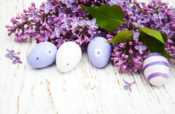 Easter eggs and fresh lilac flowers. On a old wooden background Stock Images