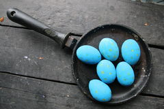Easter eggs in a frying pan on vintage table Royalty Free Stock Photos