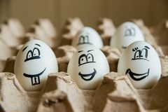 Two funny smiling eggs in a packet. Easter eggs with fun painted faces in a packet Stock Photo