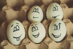 Two funny smiling eggs in a packet. Easter eggs with fun painted faces in a packet Royalty Free Stock Images
