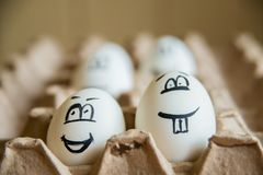 Two funny smiling eggs in a packet. Easter eggs with fun painted faces in a packet Royalty Free Stock Photography