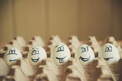 Two funny smiling eggs in a packet. Easter eggs with fun painted faces in a packet Stock Images