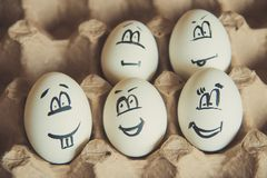 Two funny smiling eggs in a packet. Easter eggs with fun painted faces in a packet Stock Photos