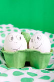 Easter eggs with funny faces in the green Stock Images