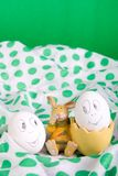 Easter eggs with funny faces near bunny on polka dot tablecloth. Stock Photo