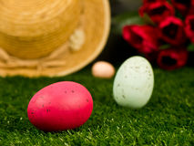 Easter Eggs in the Garden. A classic Easter egg hunt in the garden with colorful Easter eggs in the grass with a straw hat and red tulips in the background Royalty Free Stock Images