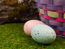 Easter Eggs in the Garden. A classic Easter egg hunt in the garden with colorful Easter eggs in the grass with a straw hat and red tulips in the background Royalty Free Stock Image