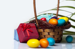 Easter eggs and gift box in wicker basket Stock Photo