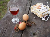 Easter eggs and glass of red wine on the table stock image