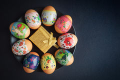 Easter eggs and golden giftbox on black plate Stock Images