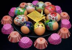 Easter eggs, golden giftbox, cupcake cups Royalty Free Stock Photos