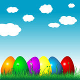 Easter eggs on the grass. Over cloudy blue sky Stock Image
