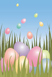 Easter eggs in grass. Easter eggs in green grass with smaller Easter eggs floating in a gradient blue sky in the background Stock Photos