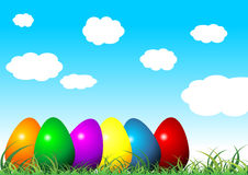 Easter eggs on grass. With different colors over cloudy blue sky Royalty Free Stock Photography