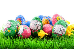 Easter eggs on grass. Colorful chocolat easter eggs on grass, isolated on white background royalty free stock photos