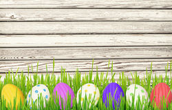 Easter eggs and grass border on wood. Easter eggs and grass border on white wooden background Royalty Free Stock Image
