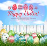 Easter eggs on a grass field with flower on wooden white fence background. Illustration of Easter eggs on a grass field with flower on wooden white fence Stock Photo