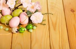 Easter eggs, grass, flowers, candy on background light wood. Easter eggs, grass, branch with flowers, candy on the background of light wood Stock Images
