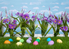 Easter eggs on grass, flowers on fence, sky background Stock Photo