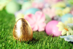 Easter eggs on grass with golden egg Stock Images