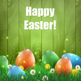 Easter eggs and grass with a green wooden background. Ester greeting card Stock Photos