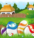 Easter eggs in the grass and rural houses Stock Images