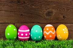 Easter eggs on grass with a rustic wood background Stock Photo