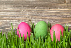 Easter eggs in the grass. On rustic wooden background Stock Photo