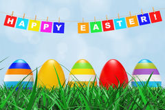Easter Eggs in Grass under Happy Easter Sign hanging on Rope. 3d Stock Image