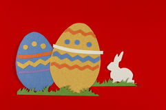 Easter eggs with grass and white rabbit. Colorful eggs with grass and rabbits drawn and cut on paper, easter egg on a red background royalty free stock photo