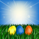 Easter eggs on the green grass. Against the blue sky with the sun Royalty Free Stock Photography