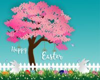Easter eggs on green grass in the garden with white rabbits,little daisy and butterfly under sakura tree on soft blue background. Paper art and digital craft Stock Photo