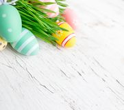 Easter eggs in green grass on white wooden background.  Handmade. Painted festive eggs. Happy Easter Stock Photos