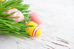 Easter eggs in green grass on white wooden background.  Handmade. Painted festive eggs. Happy Easter Royalty Free Stock Photography