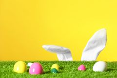 Easter eggs on green lawn and funny bunny ears against color background. Space for text royalty free stock photo