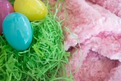 Three Easter eggs - yellow-pink-blue- on green grass and pink background stock images