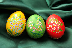 Easter Eggs on Green Satin Fabric. Three Easter eggs (red, yellow and green) lying on dark green satin fabric - textile Royalty Free Stock Photography