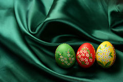 Easter Eggs on Green Satin Fabric. Three Easter eggs (red, yellow and green) lying on dark green satin fabric - textile Stock Image