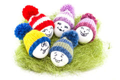 Easter eggs on green sisal. Emoticons in knitted hat with pom-po Royalty Free Stock Images