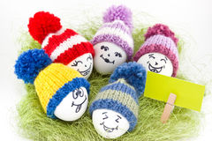Easter eggs on green sisal. Emoticons in knitted hat with pom-po Stock Image