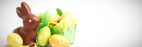 Easter eggs in a basket with chocolate bunny. Easter eggs in a green wicker basket with chocolate bunny stock image