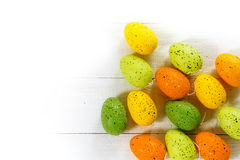 Easter eggs in green, yellow and orange on white wood, corner ba Royalty Free Stock Photos
