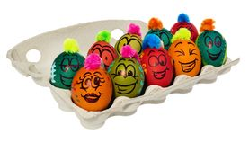 Easter eggs, hand-painted with smiling and terrified cartoon fac. Es. Decorated eggs with funny colorful hairstyles put in a cardboard box, container for eggs Royalty Free Stock Photos